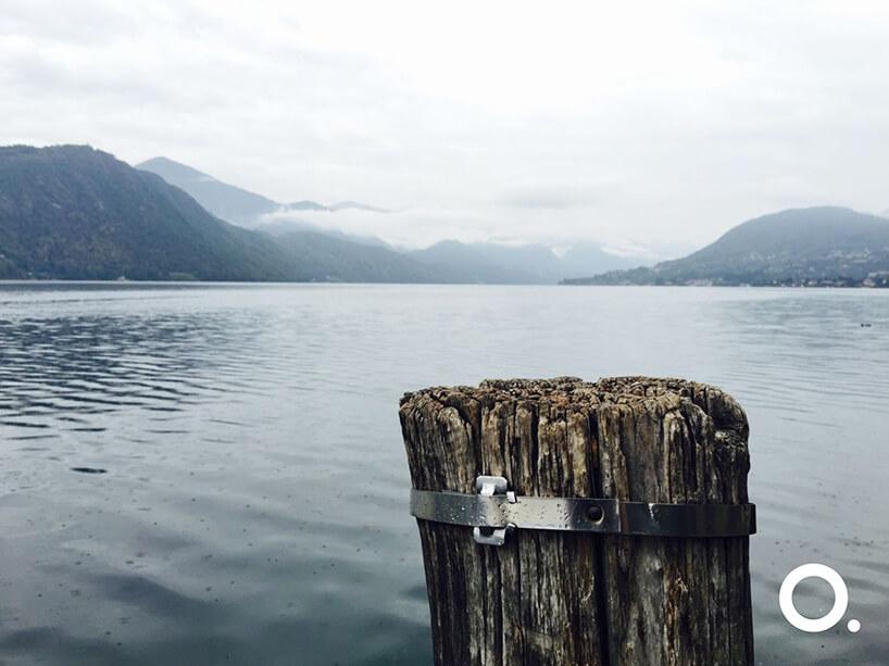 zdjęcie drewnianego słupa do cumowania na tle jeziora otoczonego zamglonymi górami