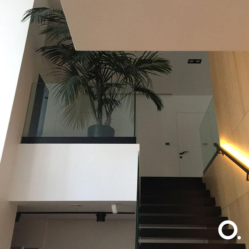 czarne schody przy drewnianej ścianie zpodświetloną poręcz