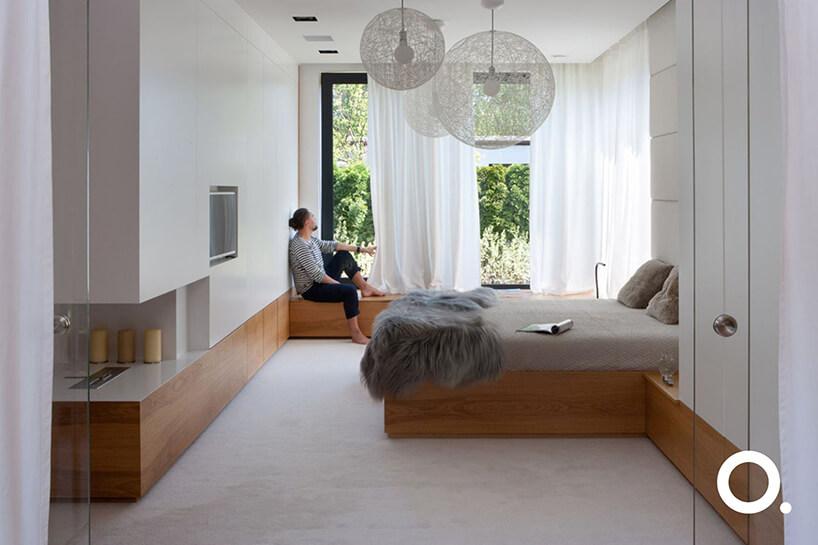 mężczyzna siedzący na niskim drewnianym parapecie wbiałej sypialni zdrewnianymi akcentami