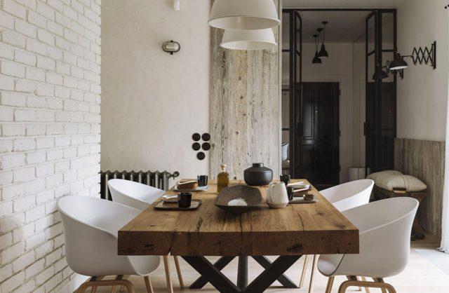 jasne wnętrze jadalni z dużym stołem z drewnianym grubym blatem z białymi plastikowymi fotelami na drewnianych nogach