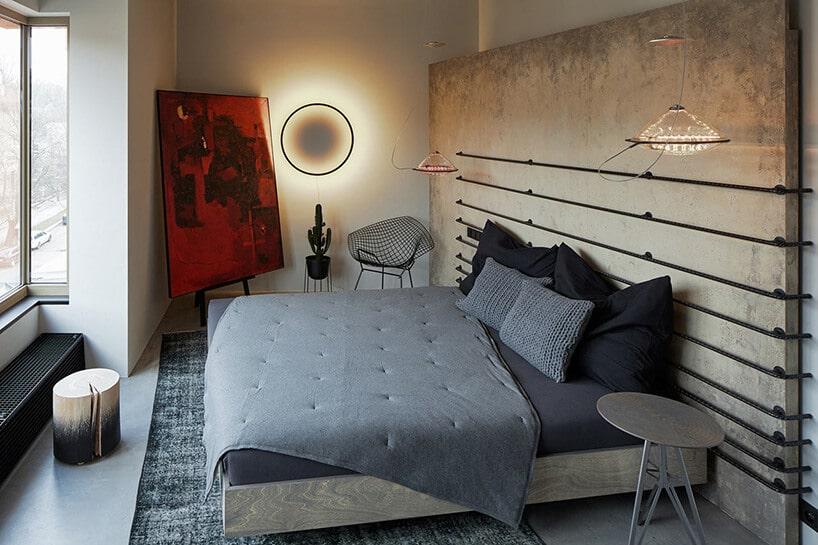 sypialnia zdużym łóżkiem oraz zagłowkiem wkolorze szarym oraz wiszący na ścianie okrąg świecący'