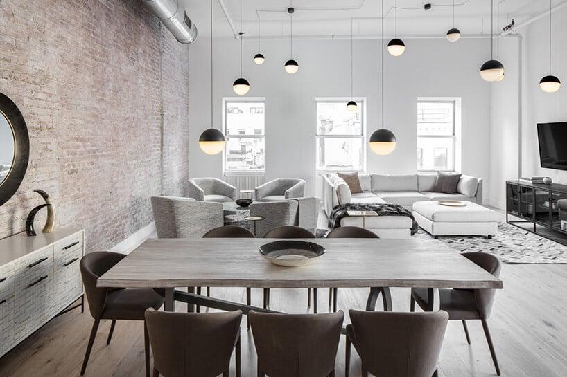 okrągłe lampy wcałym pomieszczeniu na długich sznurkach przy stołach zszarymi krzesłami