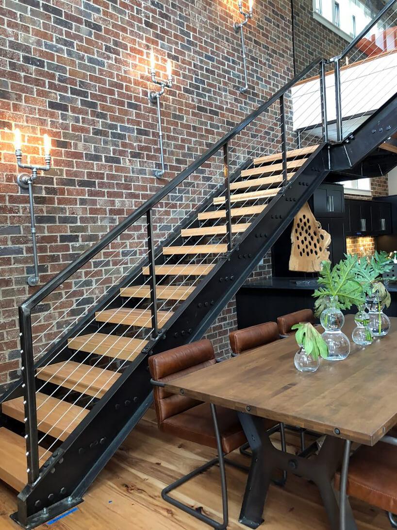 loft styl industrialny schody na antresolę na tle ceglanej ściany