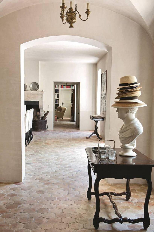 styl prowansalski wbiałym korytarzu popiersie na starym stole zzałożonym kapeluszem