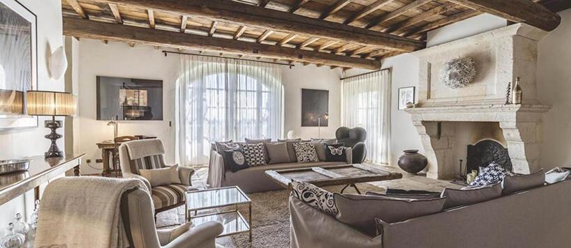 styl prowansalski wdużym salonie drewniany sufit duży kominek drewniany stół ze starych drzwi