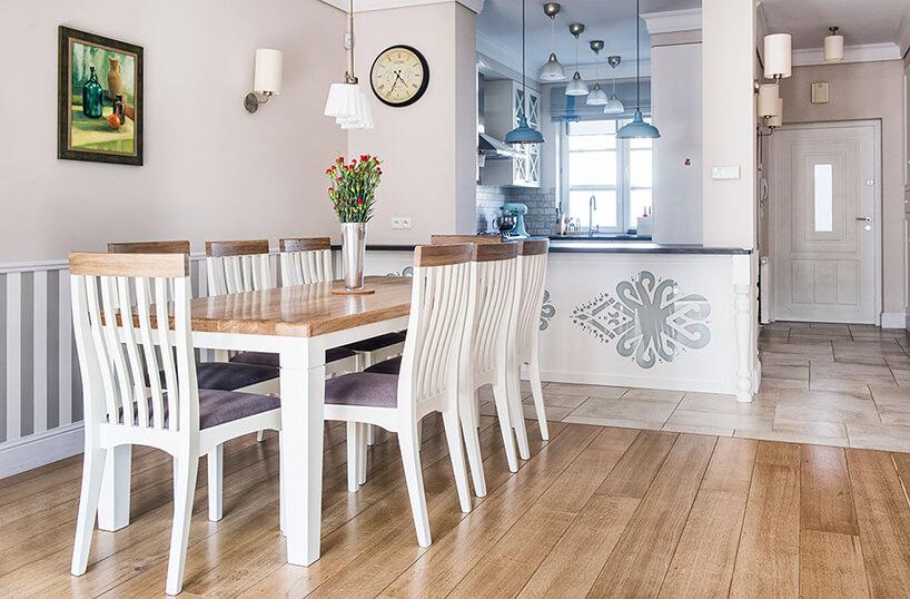 styl prowansalski wjadalni biało-szare krzesła przy dużym drewnianym stole na tle białej kuchni