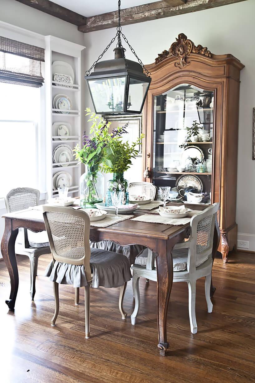 styl prowansalski wjadalni drewniany stół na tle wysokiej drewnianej szafki