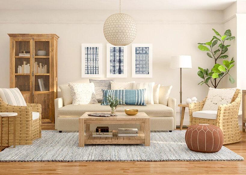jasno kremowe pomieszczenie zdużą sofą zniebieską poduszką wpaski przy małym stoliku kawowym wjasnym kolorze