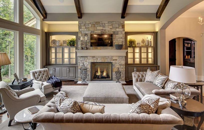 przytulne wnętrze zdużym oknem oraz kanapami oraz fotelami wszarym beżu oraz pikowaniu