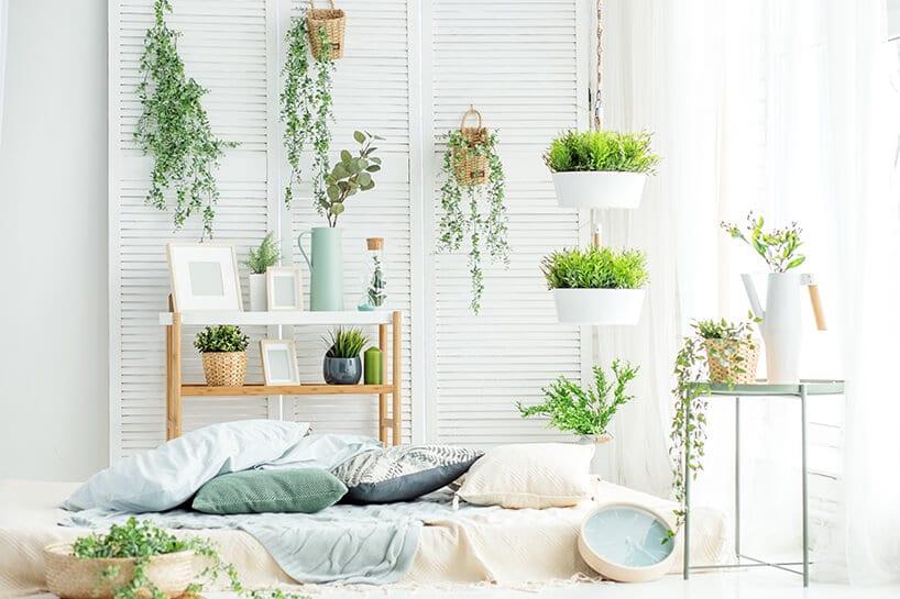 biały parawan zbiałymi paroma doniczkami zzielonymi kwiatami przy łóżku zroślinną pościelą