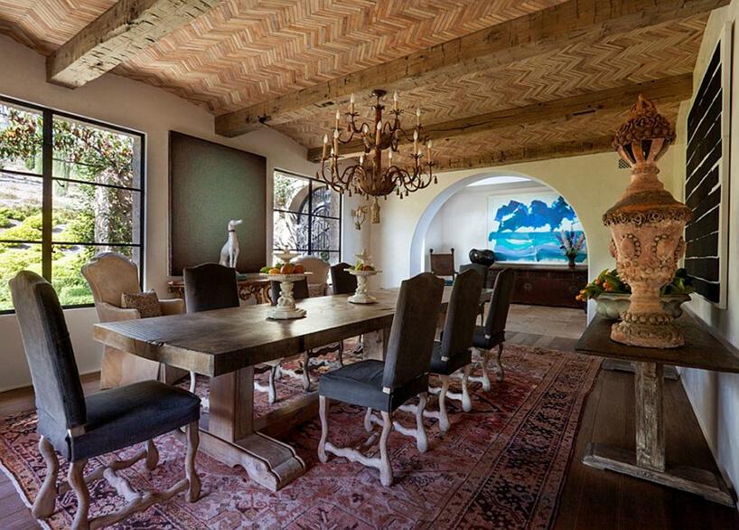 styl toskański jadalnia zdużym drewnianym stołem pośród dzieł sztuki