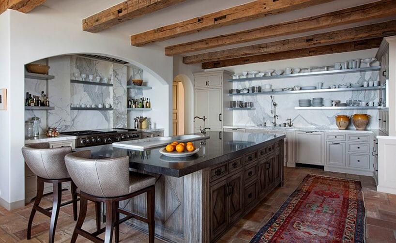 biała kuchnia wstylu prowansalskim iduża drewniana wyspa zkamiennym blatem