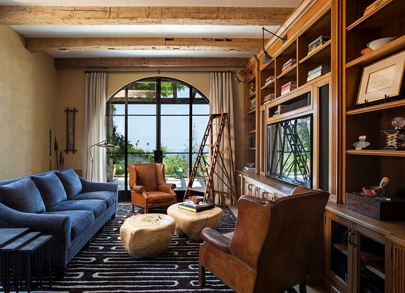 salon wstylu prowansalskim zdrewnianą zabudową dużym oknem iniebieską sofą obok dwóch skórzanych foteli