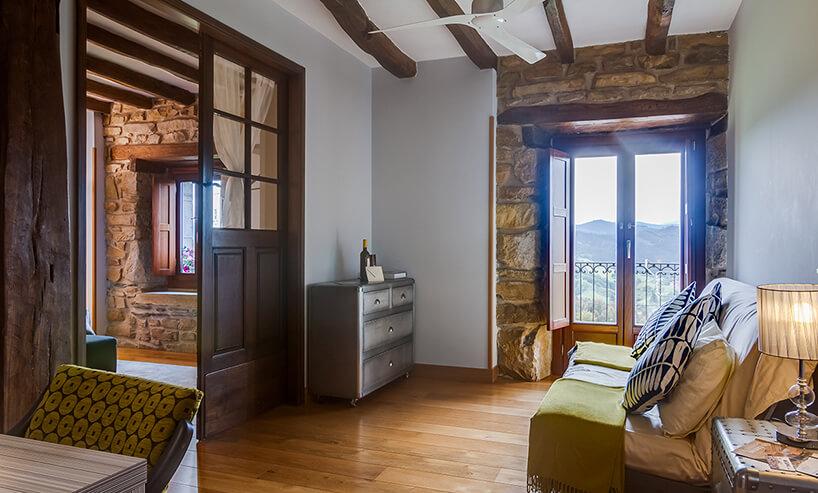mały pokój wstylu prowansalskim zbalkonem zodsłoniętym budulcem ściany