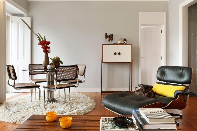 świetny salon vintage zretro fotelem obok retro stolika zkrzesłami