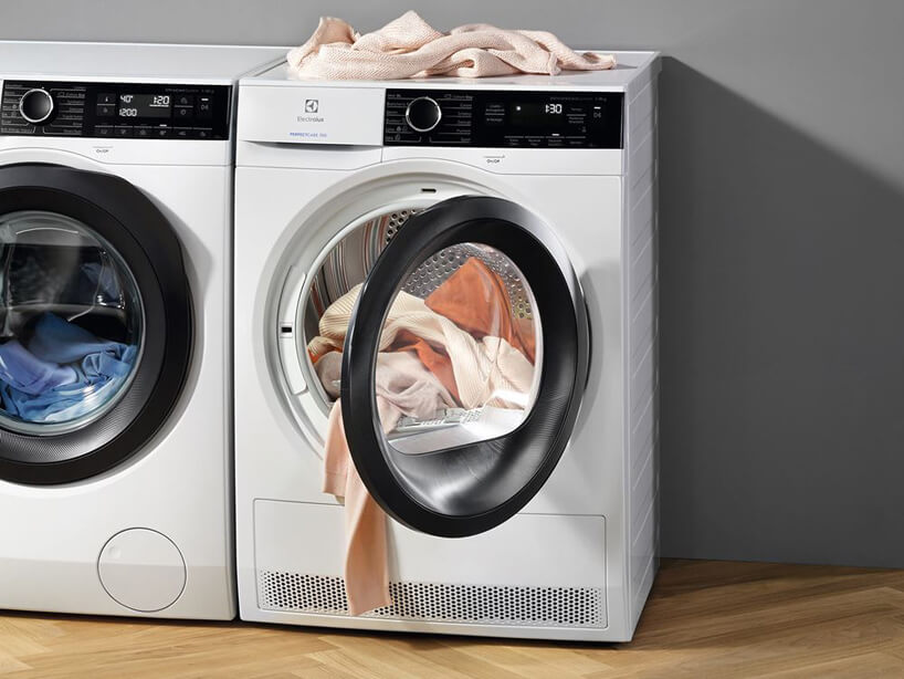 nowoczesna biała inteligetnea suszarka do ubrań marki Electrolux zotwartym drzwiczkami obok pralki marki Electrolux