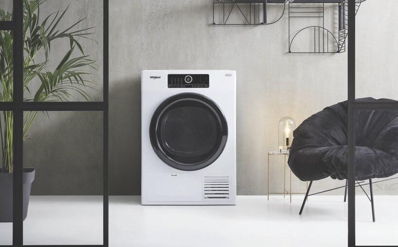 nowoczesna elegancka biała suszarka do ubrań marki Whirpool zczarnymi drzwiczkami wszarej łazience