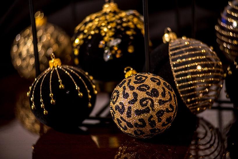 czarno złote bombki na ciemno brązowym stole