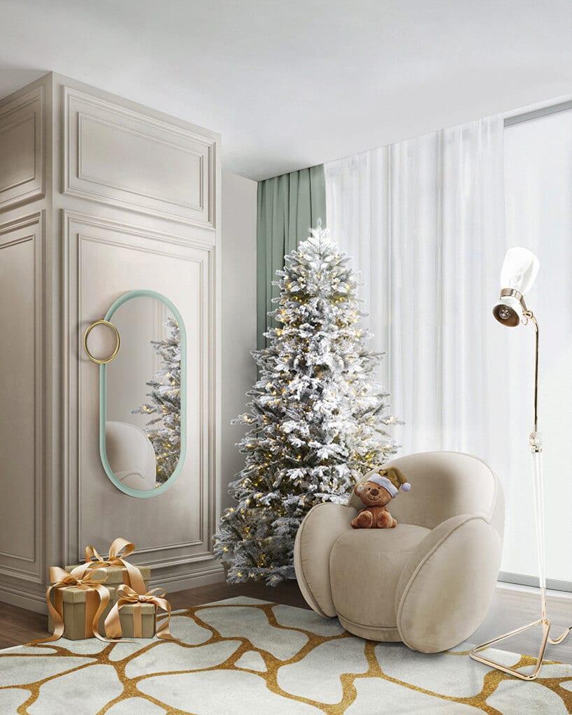 zaokrąglany beżowy fotel zmałym misiem wczapce obok ośnieżonej choinki na biało złotym dywanie obok prezentów