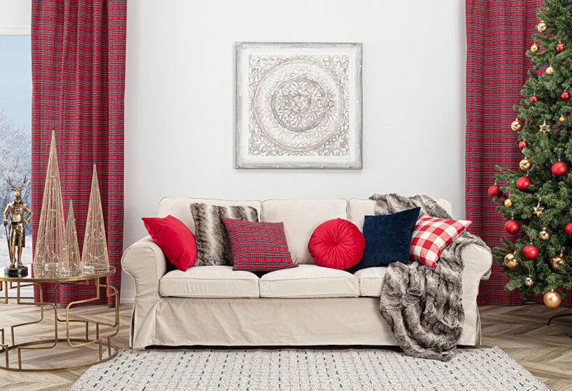 szeroka beżowa kanapa zczerwonymi iniebieskimi poduszkami oraz tygrysim kocem obok dużej zielonej choinki