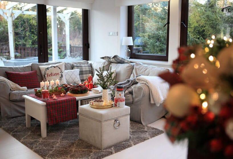 przytulny salon zciemnymi ramami okiennymi iszarą kanapą wliterę Lzozdobami