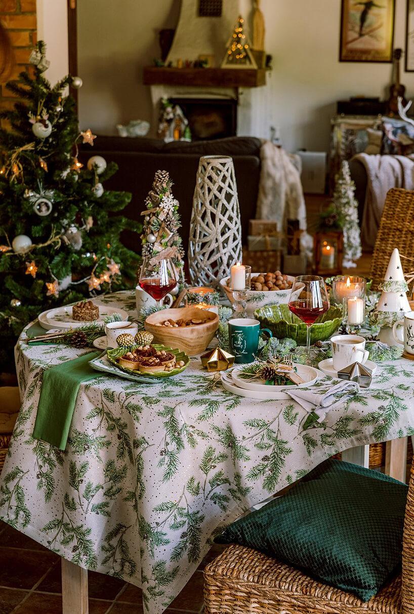 wigilijny stół zbiałym obrusem zzielonymi choinkami