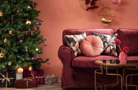 zielona choinka na tle czerwonawej ściany obok czerwonej kanapy