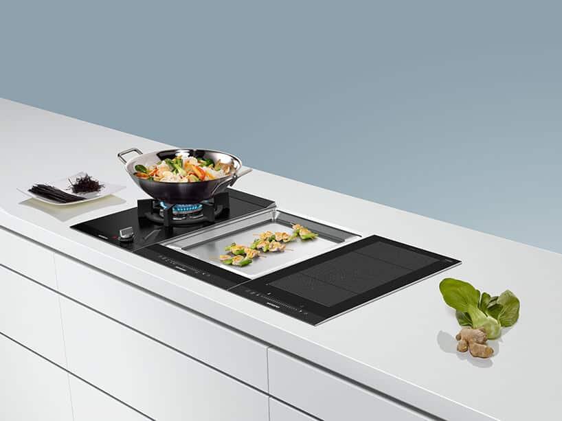 białe kuchenne szafki zczarną płytą gazową oraz indukcyjną ikamieniem grzewczym