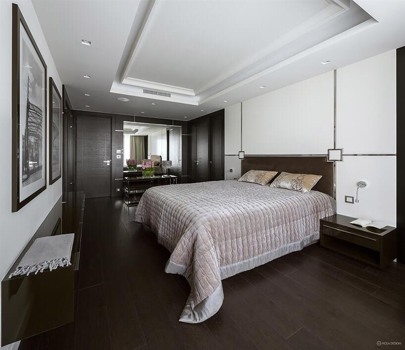 jasna sypialnia zdużym łóżkiem iciemną podłogą