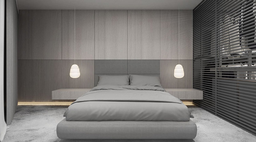 szara sypialnia zdużym łóżkiem idwoma podwieszanymi lampkami