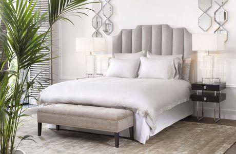 biała sypialnia z dużym łóżkiem i szarym zagłókiem