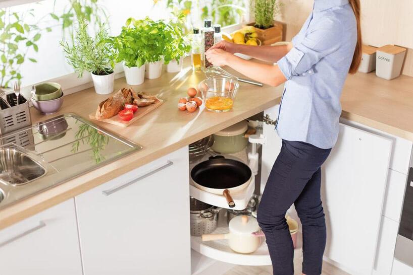 kobieta gotująca wkuchni przy drewnianym blacie ijasnych szafkach