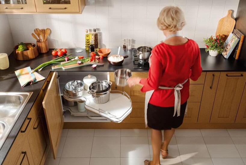 kobieta wczerwonej bluzce podziwiająca nowy system wszafce kuchennej