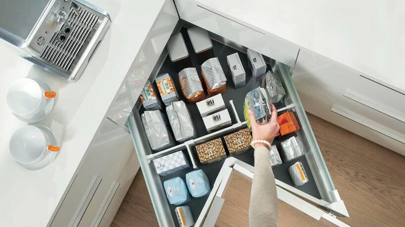duża narożna szuflada wbiałych szafkach zproduktami