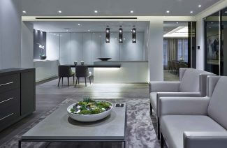 salon z szarym stolikiem i sofą na tle otwartej kuchni