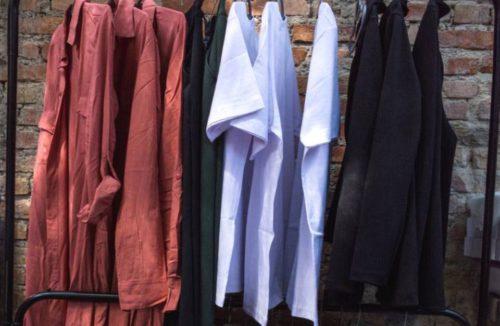 wieszak metalowy z ubraniami stojący w przedpokoju