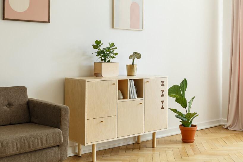 drewnianana komoda brązowa sofa na tle białej ściany zróżowo żóltymi obrazami idrewnianą podłogą