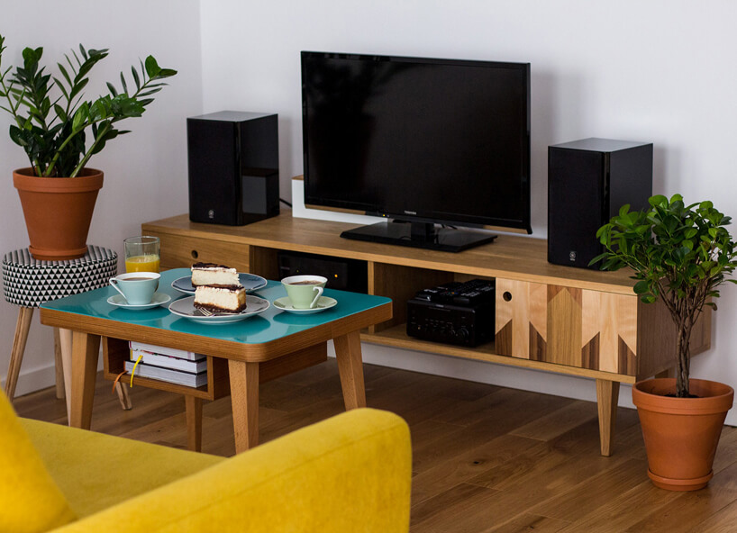 czarny telewizor igłosniki na drewnianej szafce żółta sofa niebieski drewniany stolik na tle szarej beżowej