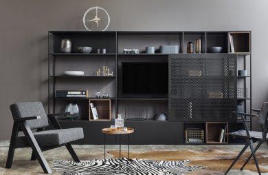 czarna metalowa szafka drewniany stoliczek i dwa krzesła na tle szarej ściany