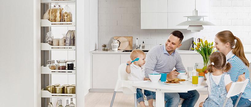 czteroosobowa rodzina siedząca przy stole wbiałej kuchni