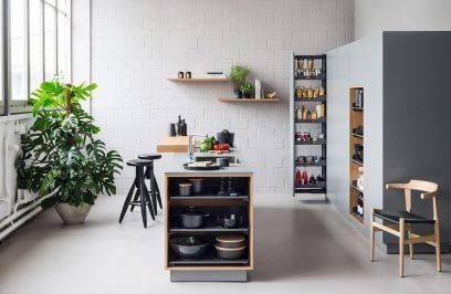 białe wnętrze kuchnii w lofcie z meblami w szarym kolorze i drewnianymi akcentami