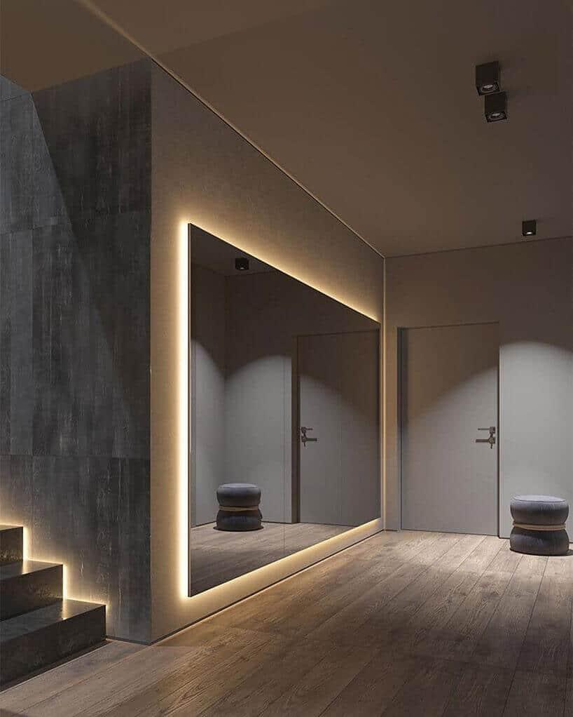 duże podświetlane lustro wszarym przedpokoju ze schodami ibiałymi drzwiami