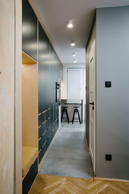przedpokój zczarnymi frontami szafy oraz wąskim korytarzem wyłożonym szarą wykładziną