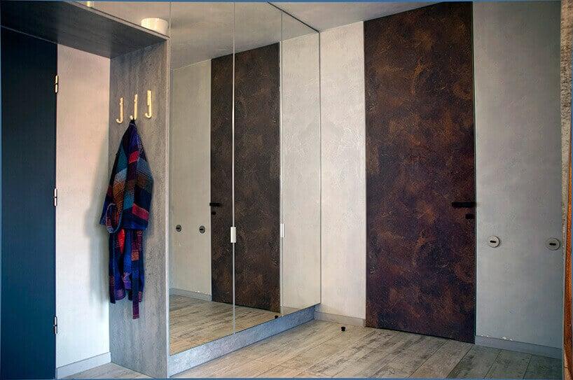 przedpokój zwysokimi drzwiami pokrytymi rdzą przy kremowej ścianie zlustrem