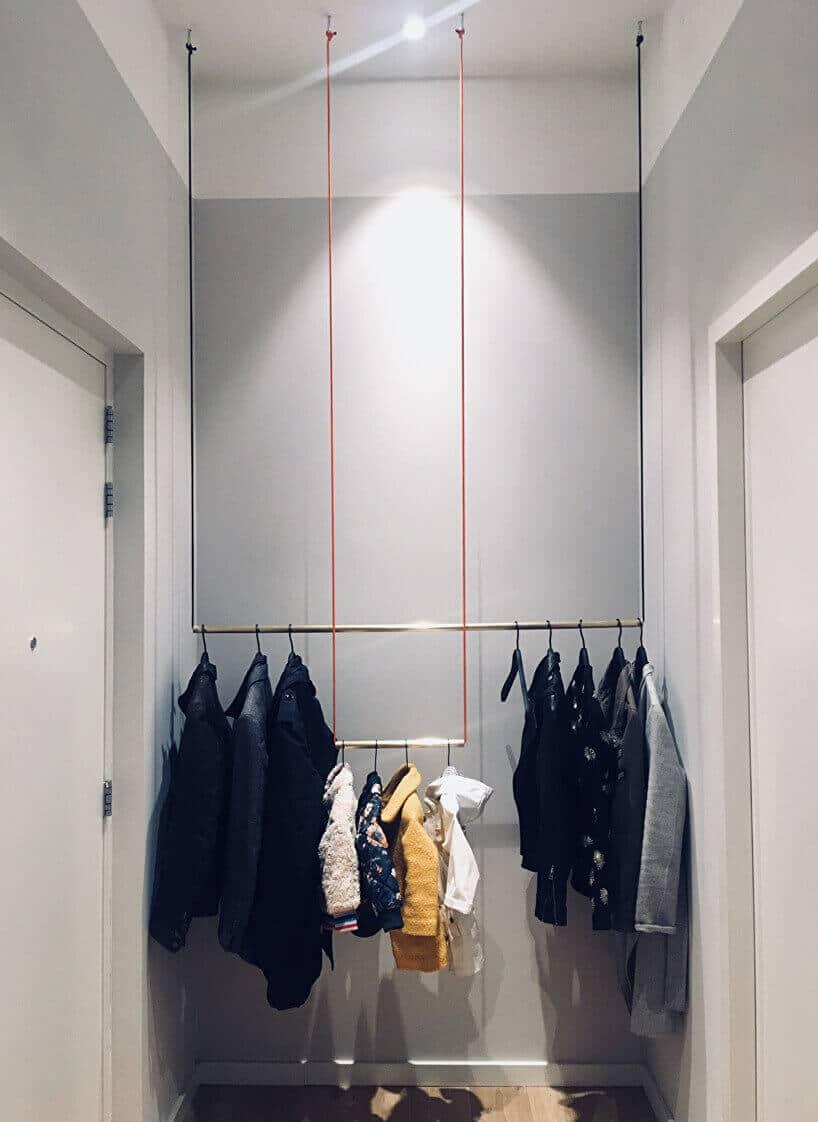 drewniane kije przymocowane na wiszących sznurach do sufitu jako wieszaki do ubrań