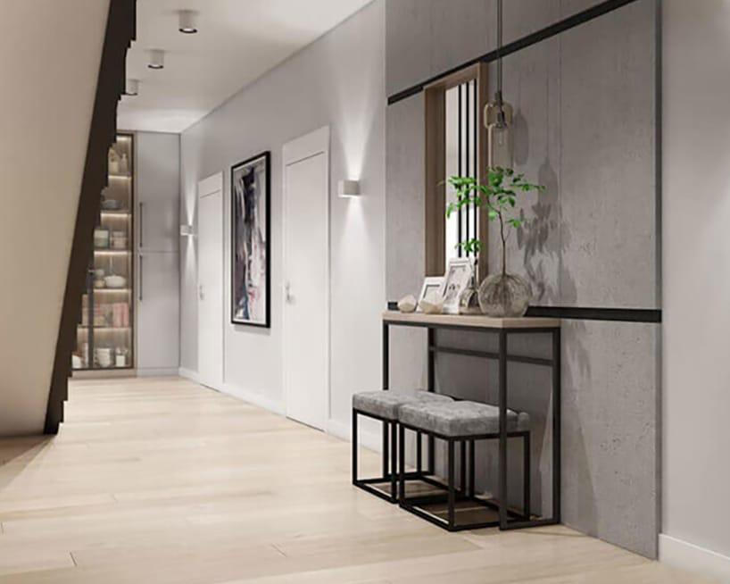 duży przedpokój zjasno drewnianymi panelami na podłodze oraz małymi siedzeniami nametalowej ramie