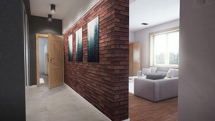korytarz zczerwoną ceglaną ściana oraz trzema obrazami wczarnych ramach