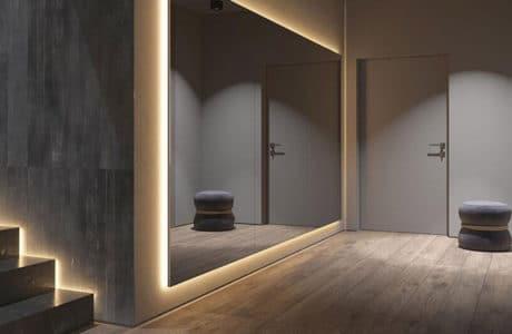 duże podświetlane lustro w szarym przedpokoju ze schodami i białymi drzwiami