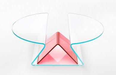 przeźroczysty stolik z powyginanego szkła z czerwonym akcentem
