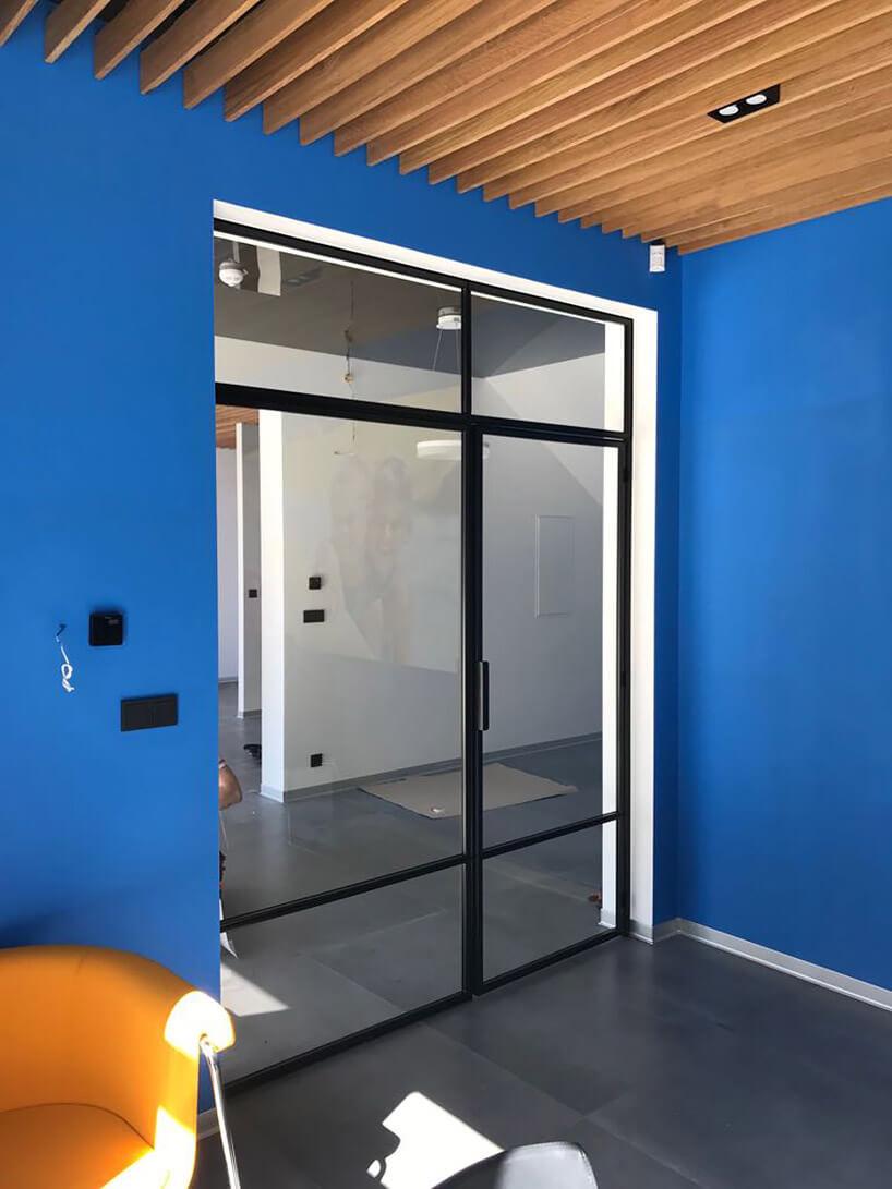 szklana ściana działowa wniebieskim wnętrzu